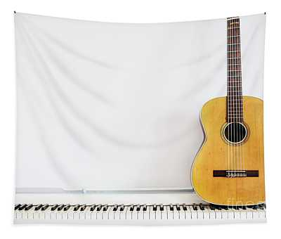 Acoustic Guitar On Piano Keyboard In Front Of White Wall. Tapestry