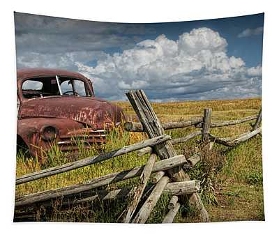 Rusted Vintage Automobile In A Rural Landscape Behind Old Wooden Log Fence Tapestry