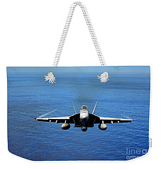 Weekender Tote Bag featuring the photograph  A Fa-18 Hornet Demonstrates Air Power. by Paul Fearn