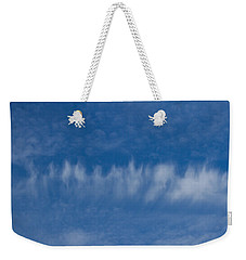 Weekender Tote Bag featuring the photograph A Batch Of Interesting Clouds In A Blue Sky by Eti Reid