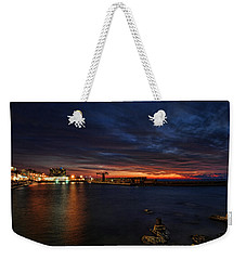 Weekender Tote Bag featuring the photograph a flaming sunset at Tel Aviv port by Ron Shoshani
