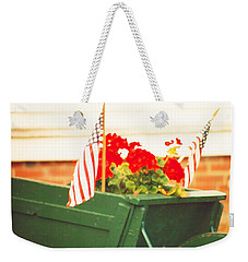 Weekender Tote Bag featuring the photograph American Flags And Geraniums In A Wheelbarrow Two by Marian Cates