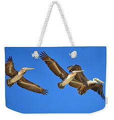 Weekender Tote Bag featuring the photograph Brown Pelicans In Flight by Debra Martz