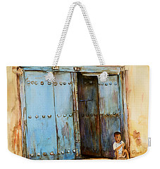 Weekender Tote Bag featuring the painting Child Sitting In Old Zanzibar Doorway by Sher Nasser