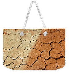 Weekender Tote Bag featuring the photograph Cracked Soil In Red Shades by Les Palenik