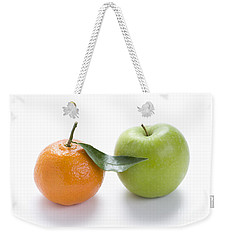 Weekender Tote Bag featuring the photograph Fresh Apple And Orange On White by Lee Avison