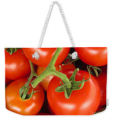 Weekender Tote Bag featuring the photograph Fresh Whole Tomatos On Vine by David Millenheft