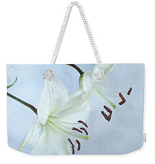 Weekender Tote Bag featuring the photograph Lilies On Blue by Louise Kumpf