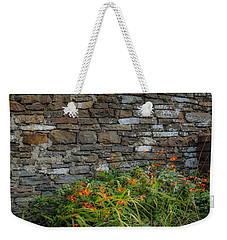 Orange Wildflowers Against Stone Wall Weekender Tote Bag