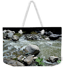 Weekender Tote Bag featuring the photograph Stream Water Foams And Rushes Past Boulders by Imran Ahmed