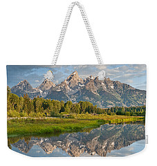 Weekender Tote Bag featuring the photograph Teton Range Reflected In The Snake River by Jeff Goulden