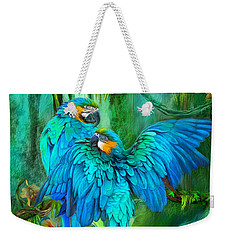 Weekender Tote Bag featuring the mixed media Tropic Spirits - Gold And Blue Macaws by Carol Cavalaris