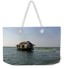 Weekender Tote Bag featuring the photograph A Houseboat Moving Placidly Through A Coastal Lagoon In Alleppey by Ashish Agarwal