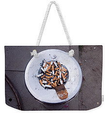 Weekender Tote Bag featuring the photograph A Lot Of Cigarettes Stubbed Out At A Garbage Bin by Ashish Agarwal