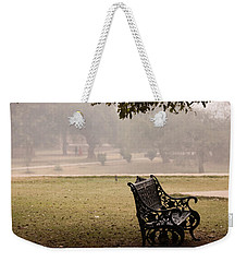 Weekender Tote Bag featuring the photograph A Wrought Iron Black Metal Bench Under A Tree In The Qutub Minar Compound by Ashish Agarwal
