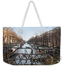 Weekender Tote Bag featuring the digital art Bikes On The Canal In Amsterdam by Carol Ailles