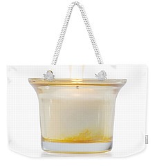 Weekender Tote Bag featuring the photograph Burning Candle In Glass Holder by Atiketta Sangasaeng