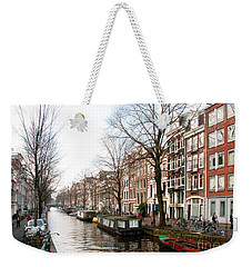 Weekender Tote Bag featuring the digital art Homes Along The Canal In Amsterdam by Carol Ailles