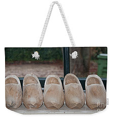 Weekender Tote Bag featuring the digital art Rows Of Wooden Shoes by Carol Ailles