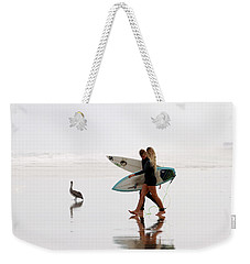Weekender Tote Bag featuring the photograph Surfers And A Pelican by Alice Gipson