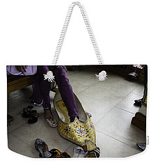Weekender Tote Bag featuring the photograph Trying On A Very Large Decorated Shoe by Ashish Agarwal