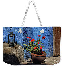 Weekender Tote Bag featuring the photograph Red Geranium Near A Blue Wall by Patricia Hofmeester