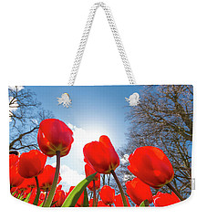 Weekender Tote Bag featuring the photograph Red Tulips Against Blue Sky by Hans Engbers