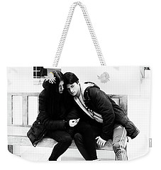 Weekender Tote Bag featuring the photograph Young Romantic Couple Sharing A Mobile Phone by John Williams