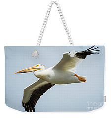Weekender Tote Bag featuring the photograph  American White Pelican Flyby  by Ricky L Jones