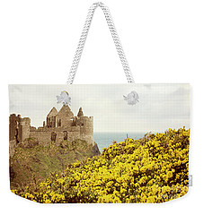 Weekender Tote Bag featuring the photograph Castle Ruins And Yellow Wildflowers Along The Irish Coast by Juli Scalzi