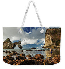 Weekender Tote Bag featuring the photograph catching fish in Atuh beach by Pradeep Raja Prints