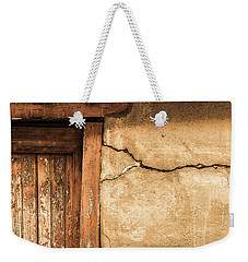 Weekender Tote Bag featuring the photograph Cracked Lime Stone Wall And Detail Of An Old Wooden Door by Semmick Photo