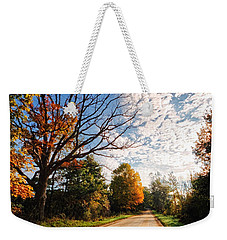 Weekender Tote Bag featuring the photograph Dirt Road And Sky In Fall by Lars Lentz