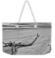 Weekender Tote Bag featuring the photograph Driftwood On The Beach In Black And White by Paul Ward