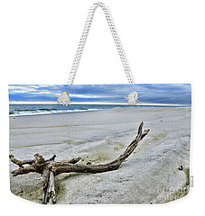 Weekender Tote Bag featuring the photograph Driftwood On The Beach by Paul Ward