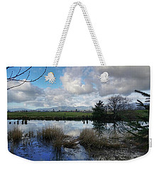 Weekender Tote Bag featuring the photograph Flooding River, Field And Clouds by Chriss Pagani