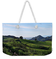 Weekender Tote Bag featuring the photograph Green Hills Purple Flowers Foreground  by Matt Harang