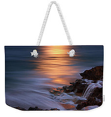 Weekender Tote Bag featuring the photograph Harvest Moon Rising Over Beach Rocks On Hutchinson Island Florida During Twilight. by Justin Kelefas