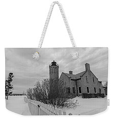 Weekender Tote Bag featuring the photograph Lighthouse And Mackinac Bridge Winter Black And White  by John McGraw