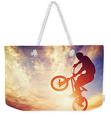 Man Riding A Bmx Bike Performing A Trick Against Sunset Sky Weekender Tote Bag