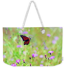 Weekender Tote Bag featuring the photograph Monarch Butterfly In Flight Over The Wildflowers by Kerri Farley