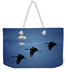 Weekender Tote Bag featuring the photograph Moonlit Flight by Susan Rissi Tregoning