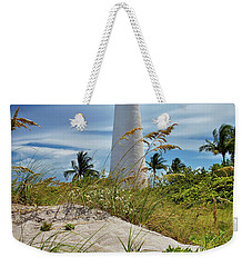 Weekender Tote Bag featuring the photograph Pelican Flying Over Cape Florida Lighthouse by Justin Kelefas