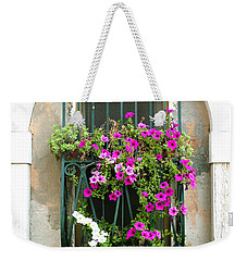 Weekender Tote Bag featuring the photograph Petunias Through Wrought Iron by Donna Corless