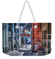 Weekender Tote Bag featuring the photograph Post Alley Straggler by Spencer McDonald