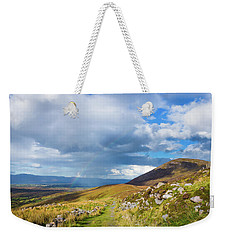 Weekender Tote Bag featuring the photograph Raining Down And Sunshine With Rainbow On The Countryside In Ire by Semmick Photo