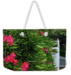 Weekender Tote Bag featuring the photograph Red Oleander Arbor by Marie Hicks