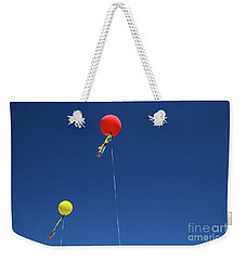 Weekender Tote Bag featuring the photograph Red,yellow Balloon Blowing By The Wind In The Air With The Blue  by Jingjits Photography