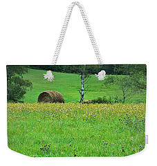 Weekender Tote Bag featuring the photograph Round Bale And Wildflowers by Joy Nichols