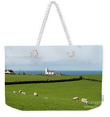Weekender Tote Bag featuring the photograph Sheep Grazing On Irish Coastline by Juli Scalzi
